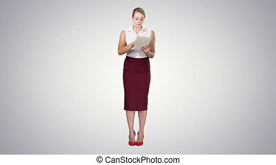Attractive businesswoman using a digital tablet while standing on gradient background.