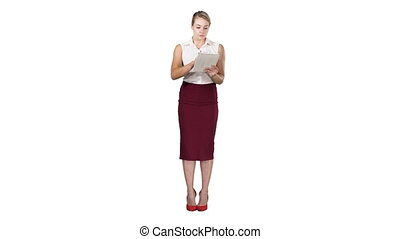 Attractive businesswoman using a digital tablet while standing on white background.