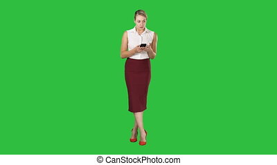 Attractive european female with smartphone in hand, touching screen with finger to type message on a Green Screen, Chroma Key.