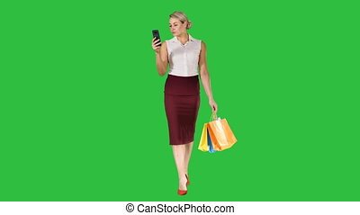 Beautiful attractive women looking in smartphone and holding shopping bags while walking on a Green Screen, Chroma Key.