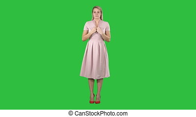Beautiful tender girl in pink dress looking at the mirror on a Green Screen, Chroma Key.