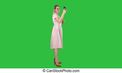 Beautiful woman preen looking to her phone on a Green Screen, Chroma Key.
