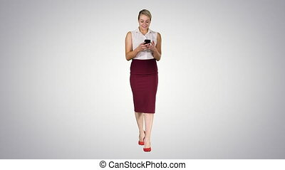 Beautiful young woman using her mobile phone on gradient background.