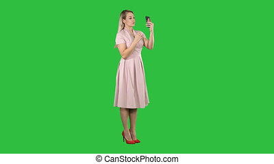Beauty woman looking at herself in her smartphone fixing her hair on a Green Screen, Chroma Key.