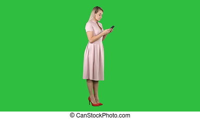 Blonde teenager woman wearing pink texting message on her smartphone on a Green Screen, Chroma Key.