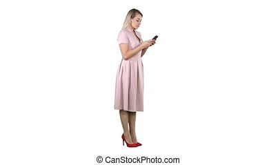 Blonde teenager woman wearing pink texting message on her smartphone on white background.