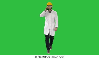 Confident male engineer wearing helmet on call on a Green Screen, Chroma Key.