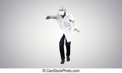 Doctor wearing his uniform and wearing a mask he is walking in a funny way on gradient background.