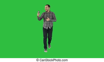 Excited man using smartphone recording video blog vlog on a Green Screen, Chroma Key.