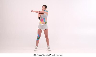 full length portrait female athletes with a kinesiotape on her body doing fitness exercises and stretching on light background
