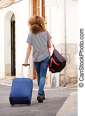 behind of female traveler with suitcase and bags walking on street