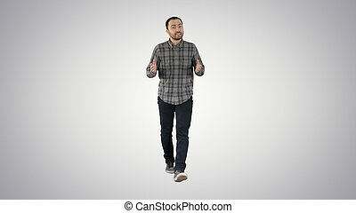 Handsome hispanic man model talking to the camera and walking on