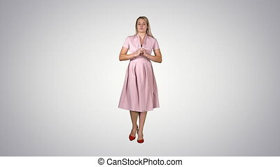 Happy young woman inpink dress is walking towards camera and...