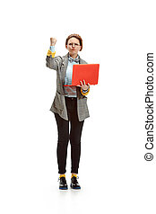 Full length portrait of a angry female student holding notebook isolated on white background
