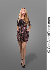 Full Length Portrait of a Beautiful Blonde Woman in Little Black Fashion Dress. Gray Background.