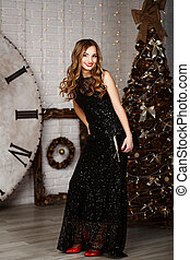 full-length Portrait of a beautiful long-haired young girl in black Evening Dress