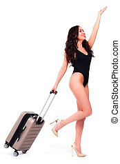Full length portrait of a beautiful smiling happy young woman in a black swimsuit standing with a suitcase, isolated on a white background, summer vacations concept