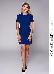 Full length portrait of a beautiful woman in blue dress