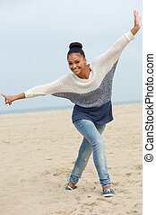 Full length portrait of a beautiful young woman with cheerful expression walking on beach with arms outstretched