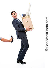 Full length portrait of a businessman carrying a cardboard box and being kicked