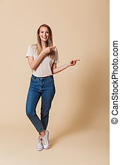 Full length portrait of a casual girl pointing finger away