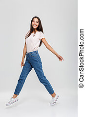 Full length portrait of a casual young asian woman jumping