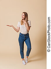 Full length portrait of a cheerful casual girl pointing finger
