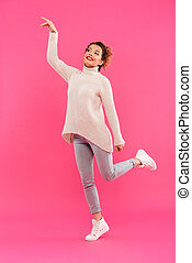 Full length portrait of a cheerful girl pointing finger away