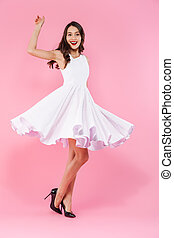 Full length portrait of a cheerful young asian woman