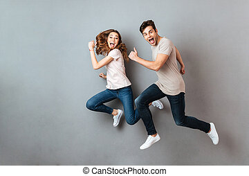 Full length portrait of a cheerful young couple jumping and...