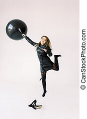 Full length portrait of a cheerful young girl in black dress holding big black air balloon while jumping and flying, looking at camera isolated over white background