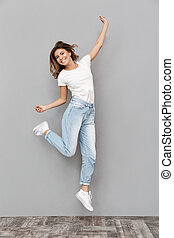 Full length portrait of a cheerful young woman jumping