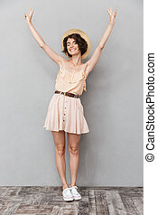 Full length portrait of a cheerful young woman