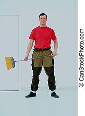 Full length portrait of a cleaner in a uniform with a broom isolated white background.