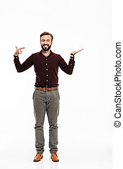 Full length portrait of a confident happy man pointing finger