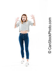 Full length portrait of a fightened girl standing and screaming
