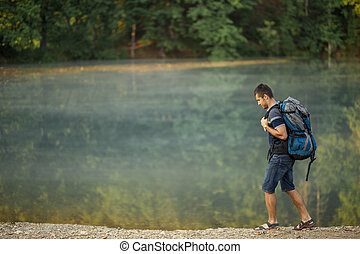 Full length portrait of a handsome hiker with backpack