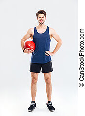 Full length portrait of a handsome sportsman with fitness ball