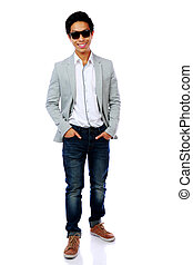Full length portrait of a happy asian man in sunglasses over white background