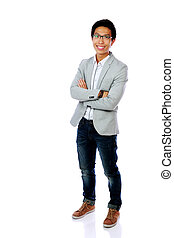 Full length portrait of a happy asian man standing with arms folded over white background