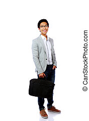 Full length portrait of a happy asian man standing with briefcase over white background