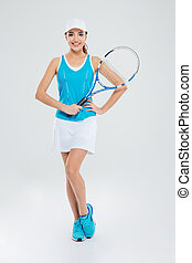 Full length portrait of a happy female tennis player