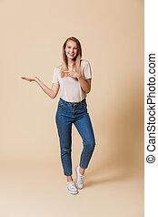 Full length portrait of a happy girl pointing finger away