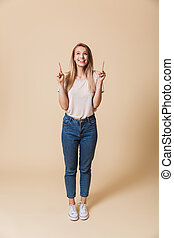 Full length portrait of a happy girl pointing finger up