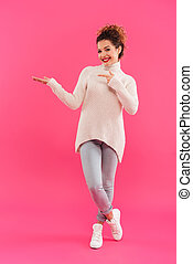 Full length portrait of a happy pretty girl pointing finger