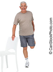 Full length portrait of a happy senior man stretching leg