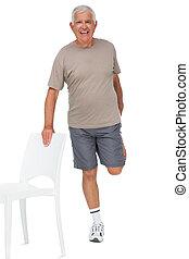 Full length portrait of a happy senior man stretching leg over white background