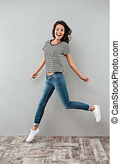 Full length portrait of a happy smiling asian woman jumping