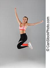 Full length portrait of a happy smiling sportsgirl...