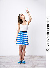 Full length portrait of a happy woman pointing up